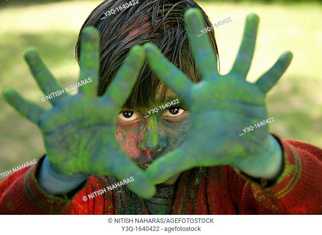 Festival of Holi is celebrated in India with colors  People smear each other with colors  A young boy shows off his colored face and hands