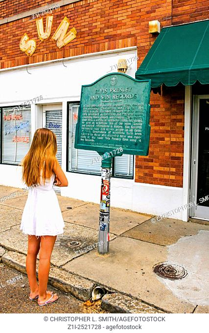 Young teenage girl reads the historic plaque outside of Sun Studio's in downtown Memphis Tennessee