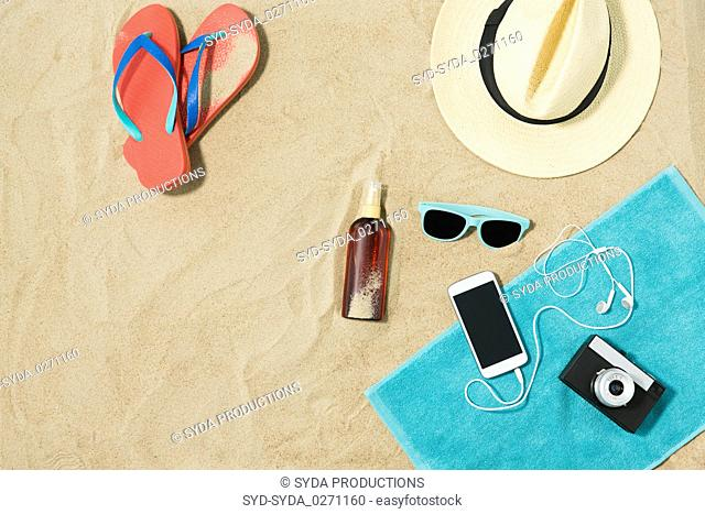 smartphone, hat, flip flops and shades on beach