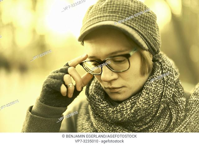 woman touching her glasses outdoors in Munich, Germany