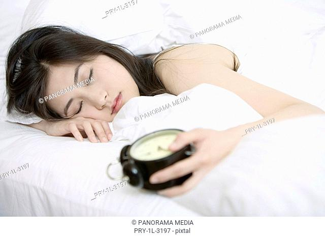 Young woman sleeping holding a alarm clock in bed