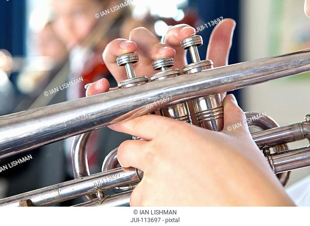 Close up high school student playing trumpet