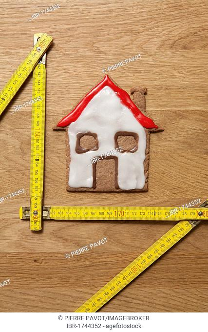 House biscuit with a measuring stick, symbolic image for home construction