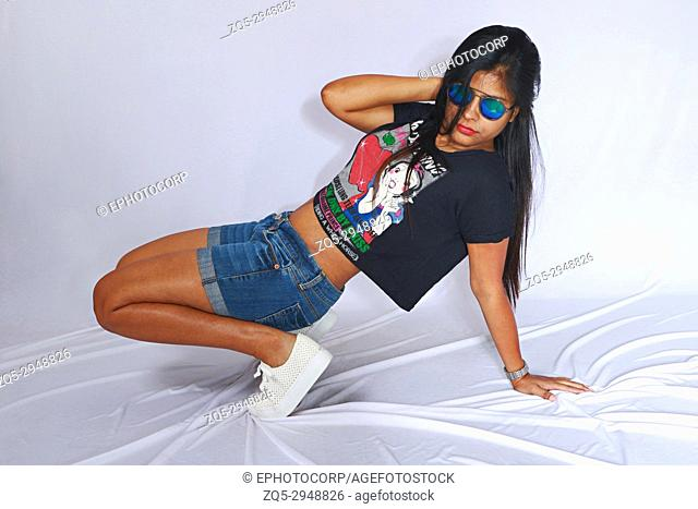 Young girl in short jean pants and goggles posing