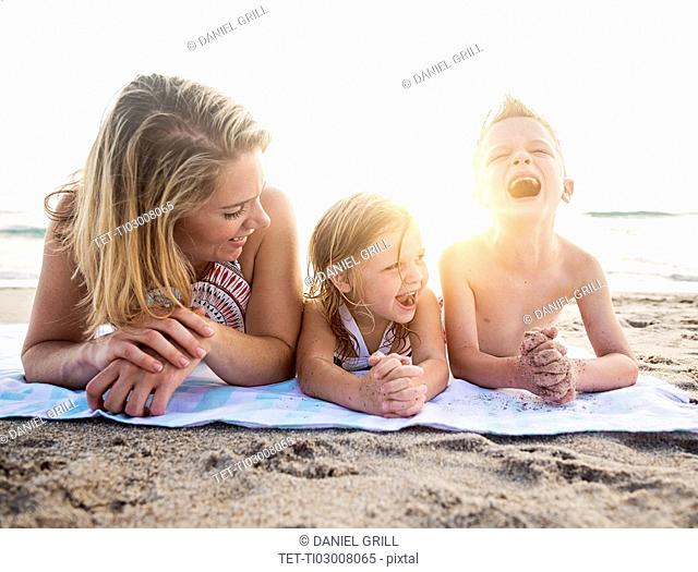 Mother lying down with son (6-7) and daughter (4-5) on beach