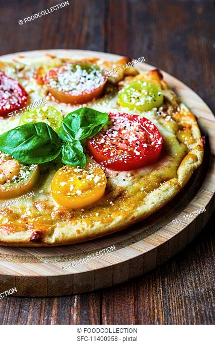 A tomato, cheese and basil pizza