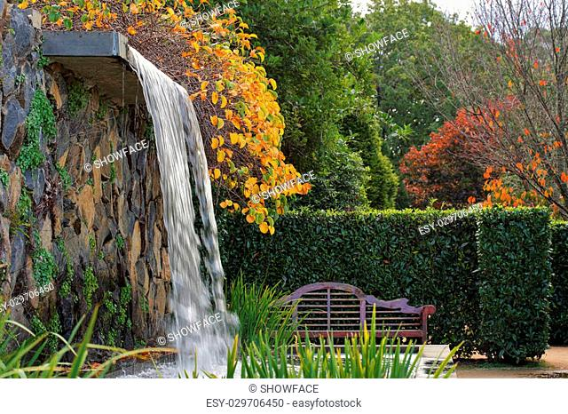 Tranquil zen garden with timber arched bench seat and sounds of cascading waters from nearby waterfal in Autumn
