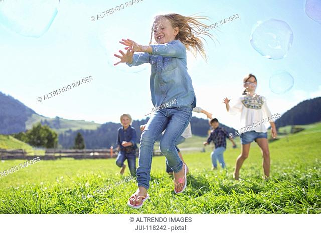 Children Chasing Giant Bubbles In Countryside