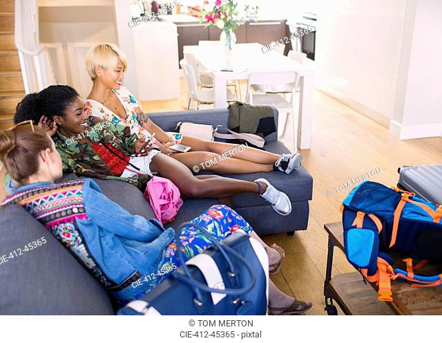 Young women friends with bags arriving at house rental