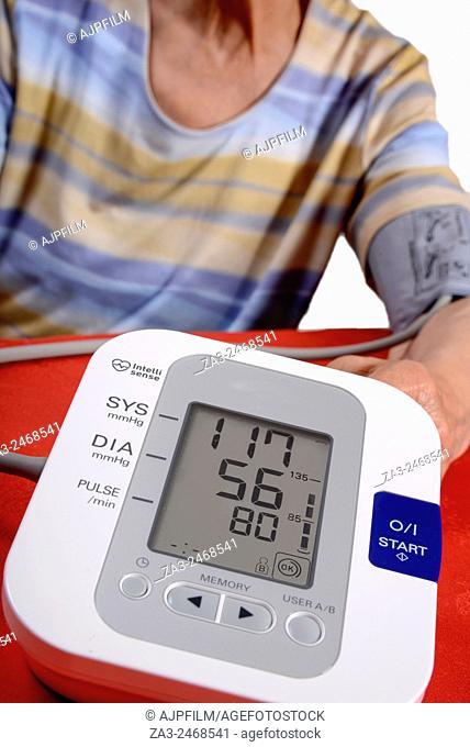 Home blood pressure testing. Elderly lady using a digital blood pressure monitor (sphygmomanometer) at home
