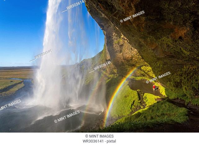 A waterfall cascade over a sheer cliff, a double rainbow in the mist
