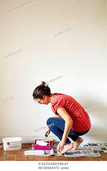 Woman kneeling, dipping paint roller into paint