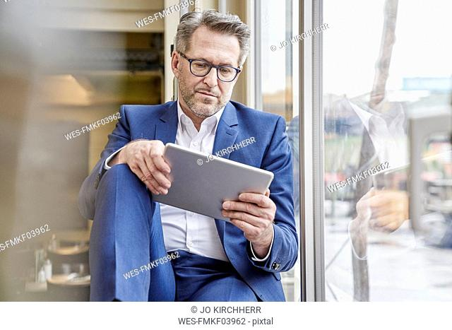 Mature businessman using tablet at the window