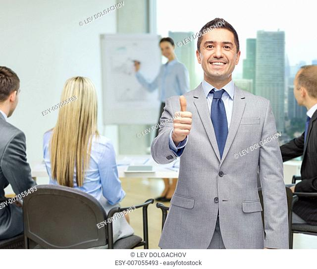 business, people, gesture and success concept - happy smiling businessman with team over office room background showing thumbs up