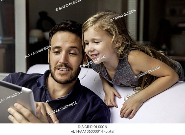 Man showing daughter video streaming on digital tablet