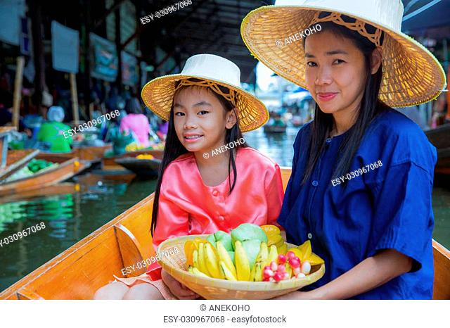 Chikd and mother sit on the boat and hold the fruit basket in Traditional floating market ,bangkok, Thailand