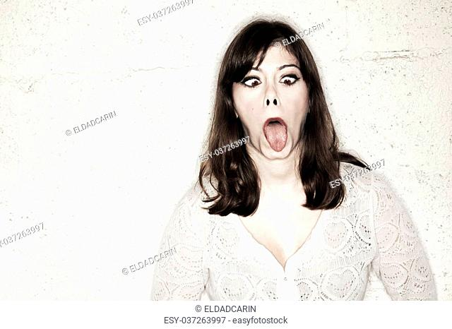 Portrait of a beautiful young woman sticking out her tongue as far as she can whilst making a goofy croos-eyed face