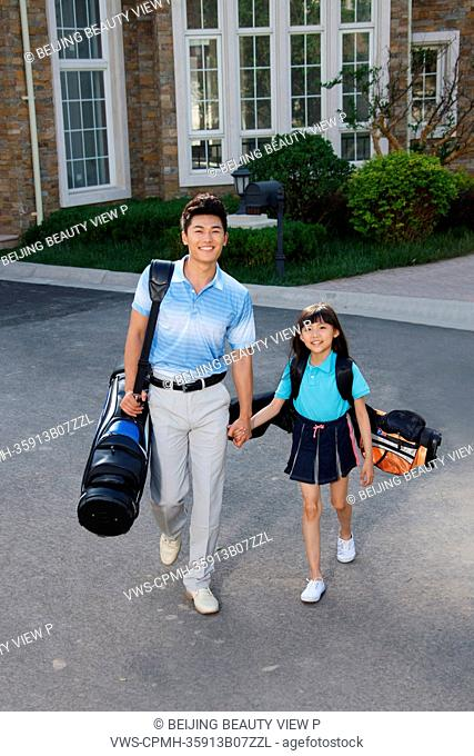 Oriental father and daughter standing with golf bag in front of villa