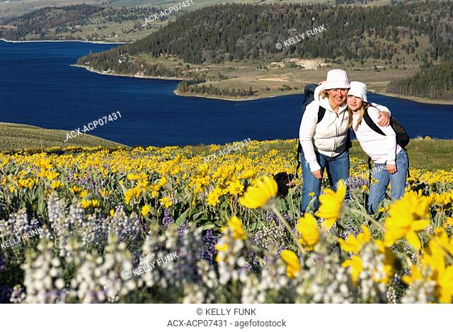 A young girl and her mother enjoy an amazing day of hiking through wildflowers at Stump Lake, near Kamloops, British Columbia, Canada