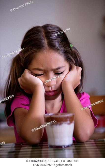 Angry girl in front of a glass with milk