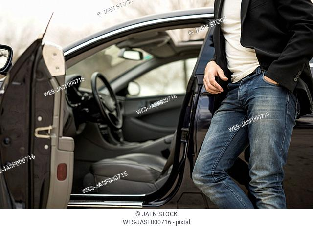 Young man leaning against car