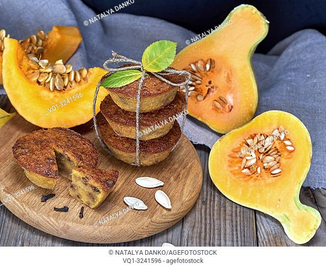 stack of muffins with a pumpkin on a round wooden board and fresh pieces of pumpkin