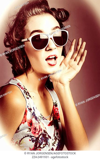Old selenium toned photograph of a beautiful surprised retro pinup woman from 1950 gasping in sun glasses with wavering hand gesture