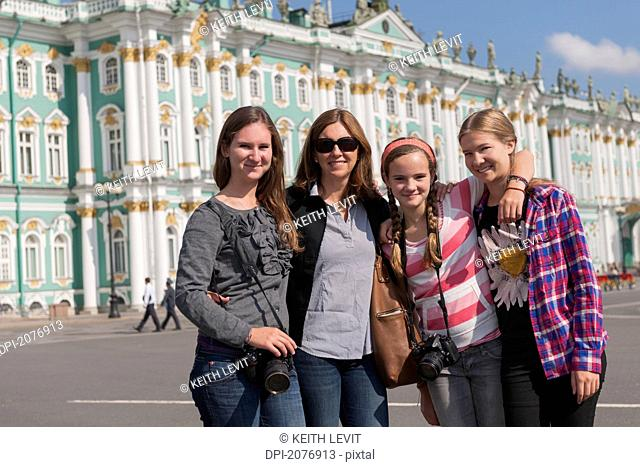 A mother and three daughters together in front of winter palace, st. petersburg russia