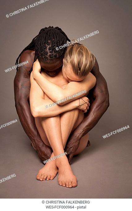 Multicultural couple sitting on ground