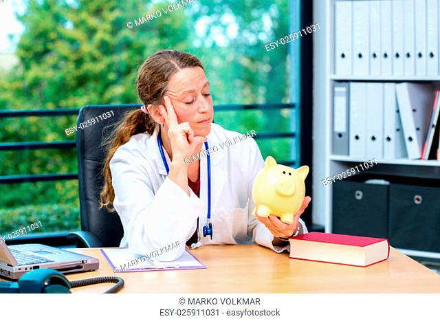 young female doctor in her office with a piggy bank