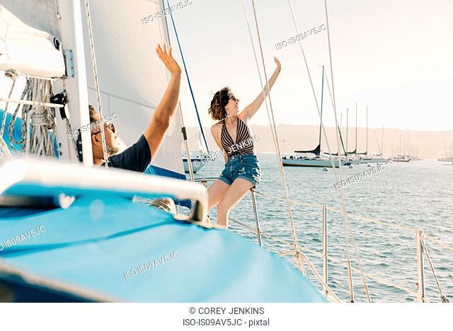 Couple waving on sailboat, San Diego Bay, California, USA