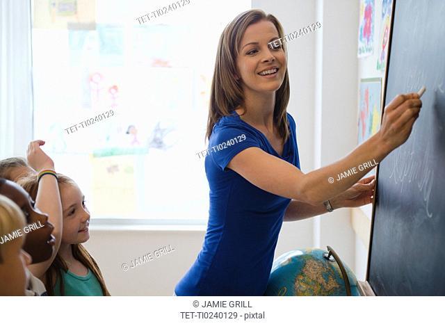 School children 8-9 with female teacher writing on blackboard