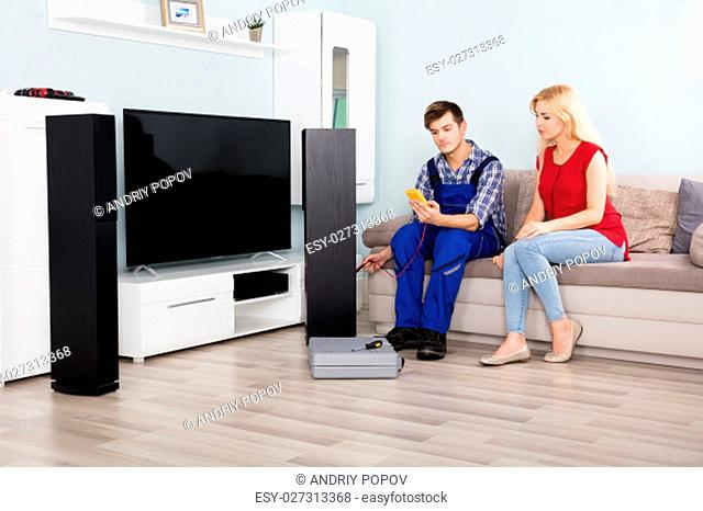 Male Technician Checking Home Theater TV Speaker In Front Of Woman On Couch At Home