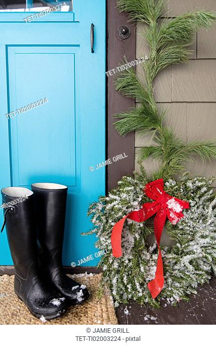 Rubber boots by blue door and wreath in christmas