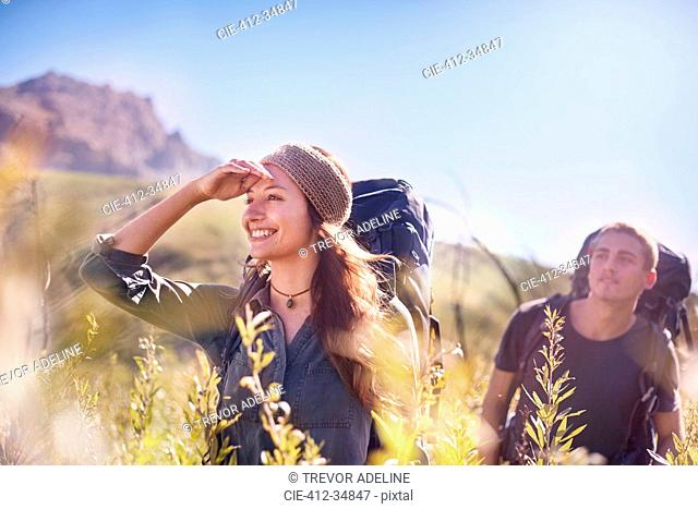 Smiling couple with backpacks hiking in sunny field