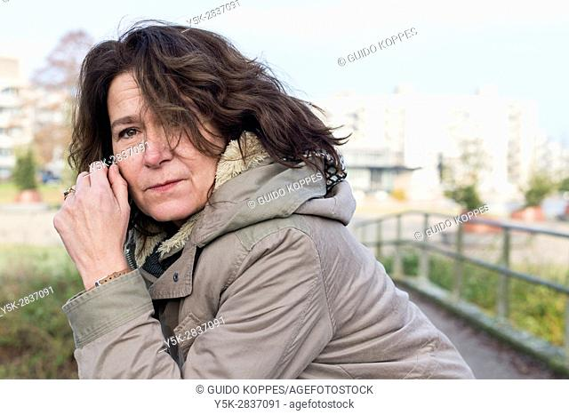 The Hague, Netherlands. Portraitof a mid adult caucasian woman leaning over a bridge railing