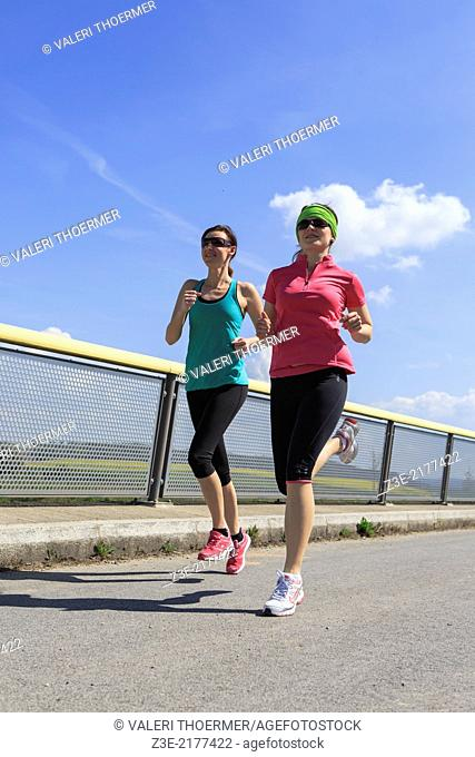 two women jogging over a bridge at the springtime