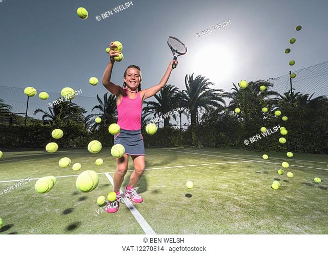 A teenage girl on a tennis court with a racquet and numerous tennis balls; Tarifa, Cadiz, Andalusia, Spain