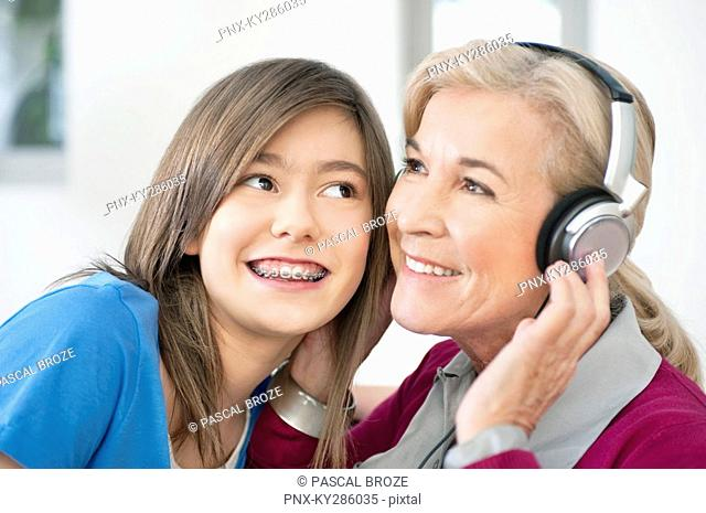 Woman with her granddaughter listening to headphones