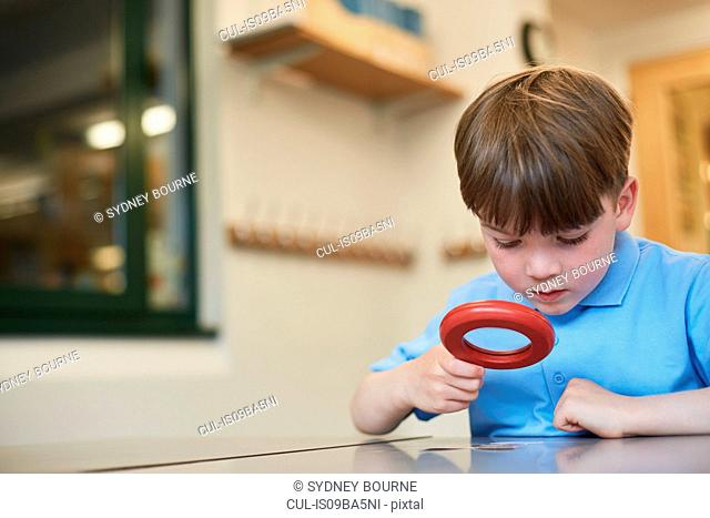 Schoolboy looking through magnifying glass in classroom lesson at primary school