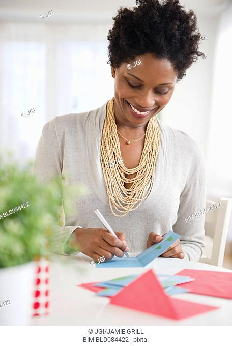 Black woman writing on birthday card