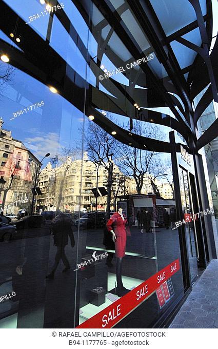 Reflection on a showcase of Mila House (La Pedrera) by Gaudi in Passeig de Gracia, Barcelona. Catalonia, Spain