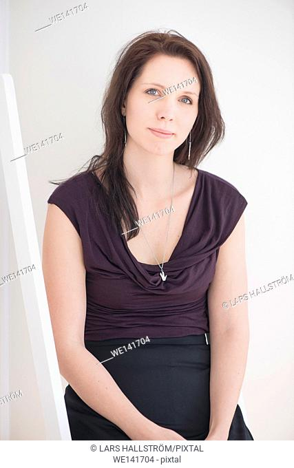 Woman sitting in home interior. Lifestyle image of young woman showing pride, relaxation and contentment