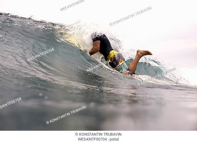 Indonesia, Java, water splashing over man surfing