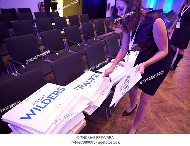 A congress employee distributes signs with the names Frauke Petry and Geert Wilders on the chairs in the room ahead of the congress of the right-wing populist...