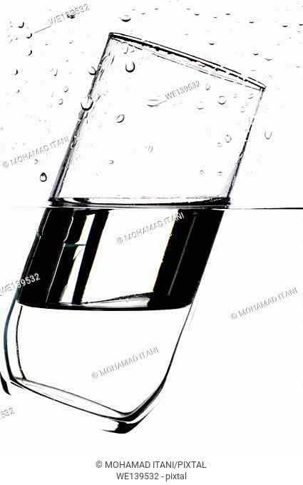 Glass floating on water with a white background