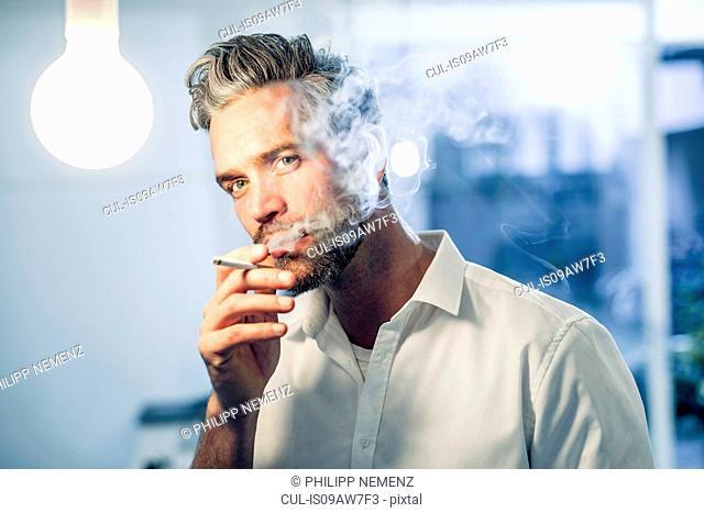 Man smoking a cigarette looking at camera