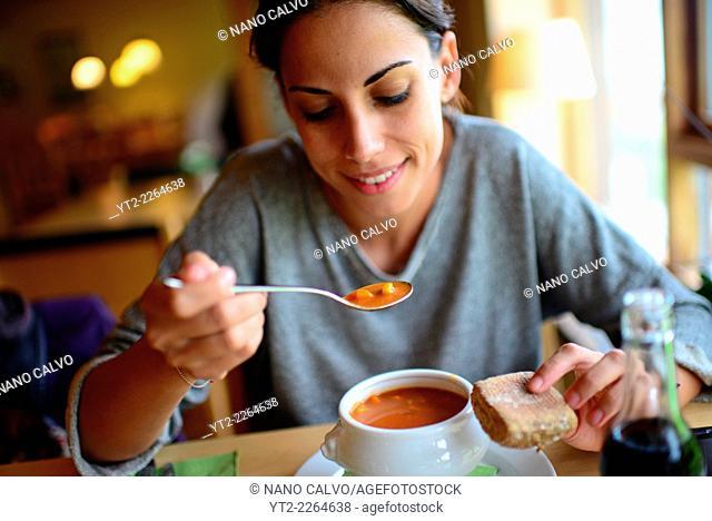 Young woman eats traditional faroese food in Gjaargardur Guesthouse, Gjógv, Faroe Islands