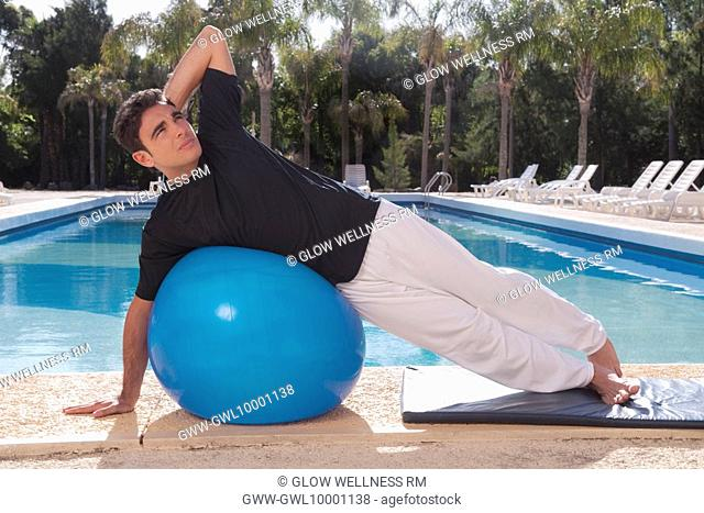 Man exercising with a fitness ball at the poolside