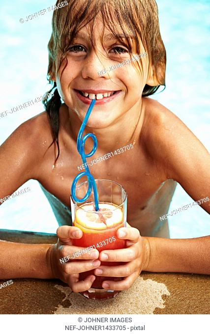 Portrait of boy in swimming pool drinking juice